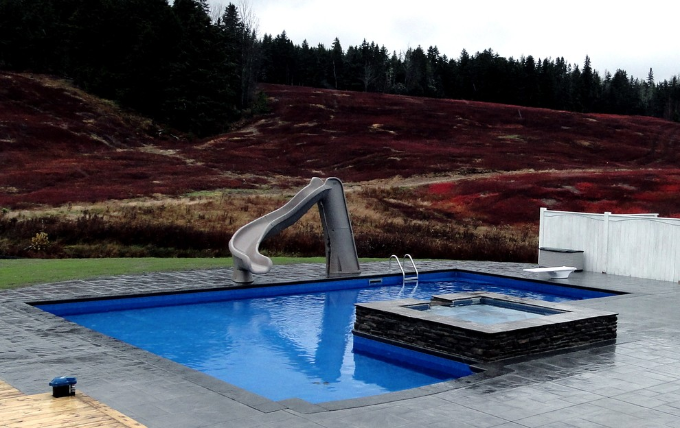 Pool - large modern backyard stamped concrete and l-shaped pool idea in Other
