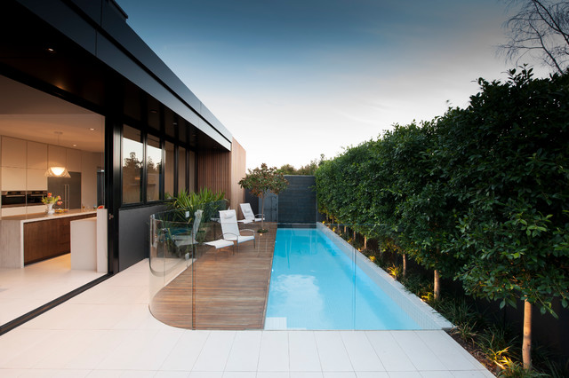 Example of a small minimalist backyard rectangular lap pool design in Melbourne with decking