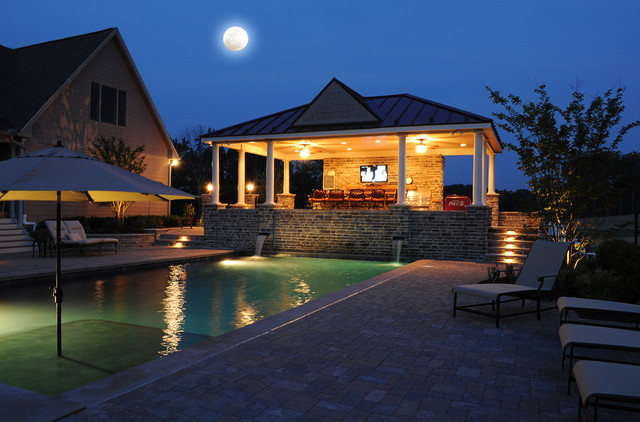 Landscape lighting of pool and poolhouse traditional pool