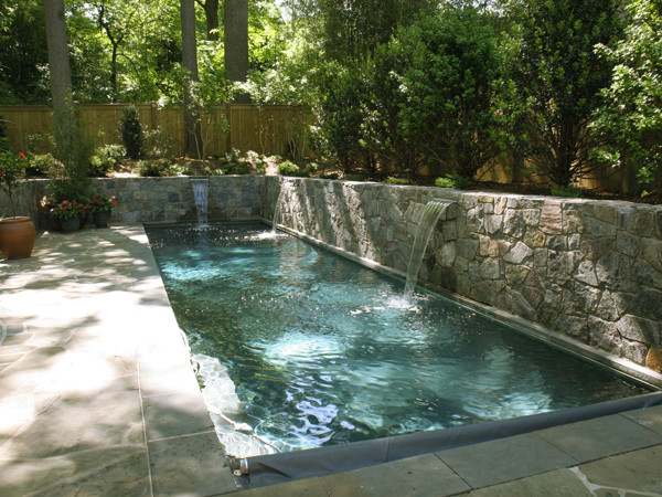Lap pool with sheer descent waterfalls and retaining walls for Pool design retaining wall