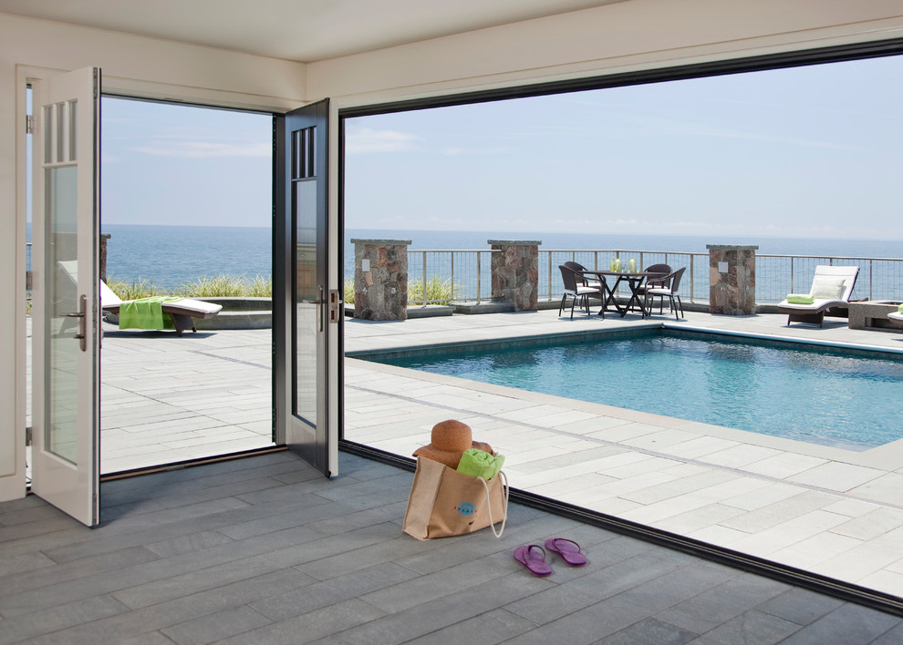 Example of a large trendy backyard stone and rectangular pool design in Boston
