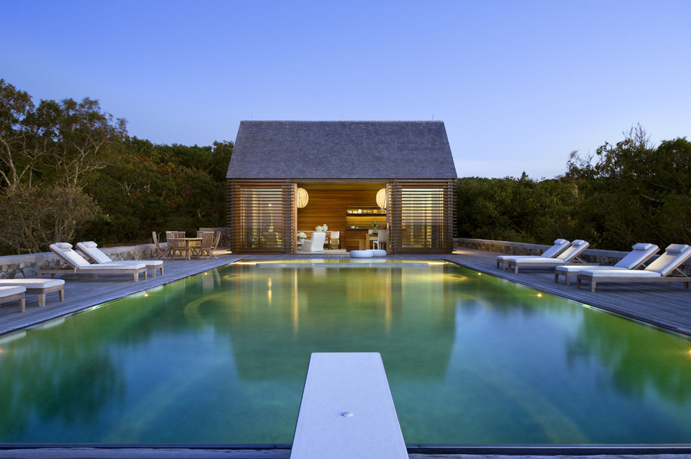 Inspiration for a mid-sized coastal backyard rectangular infinity pool house remodel in Boston with decking