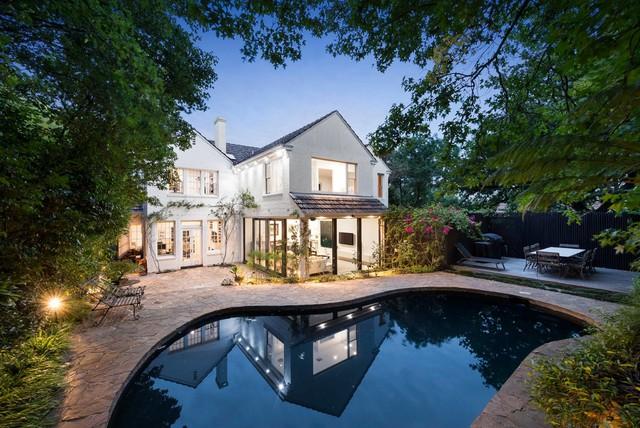 Modelo de piscina clásica renovada, a medida, en patio trasero, con suelo de baldosas