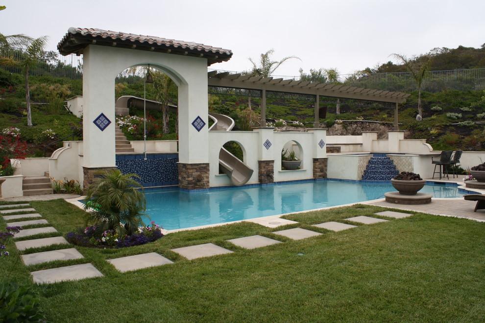 Imagen de piscina con tobogán alargada, mediterránea, grande, a medida, en patio trasero, con adoquines de piedra natural
