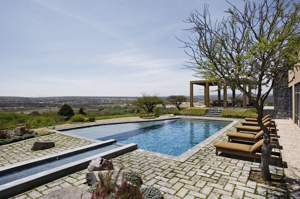 Example of a mid-sized tuscan backyard brick and custom-shaped pool design in New York