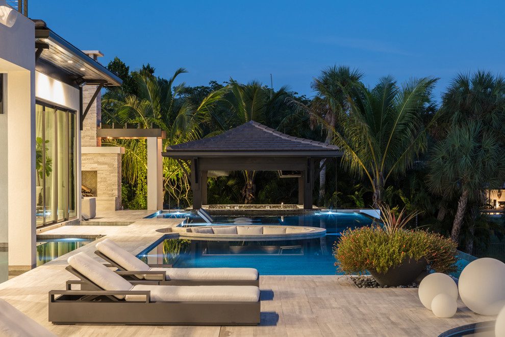 Example of a beach style backyard custom-shaped pool design in Tampa