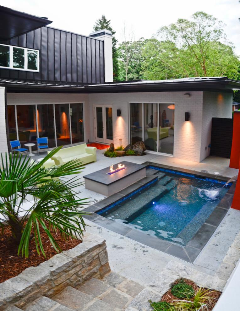Pool fountain - small modern backyard stone and rectangular pool fountain idea in Atlanta