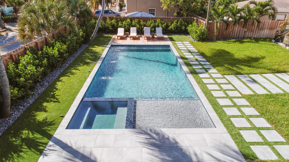 Inspiration for a mid-sized modern backyard rectangular lap hot tub remodel in Miami with decking