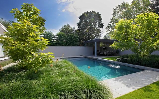 Moderne tuin met luxe veranda en zwembad en siergrassen