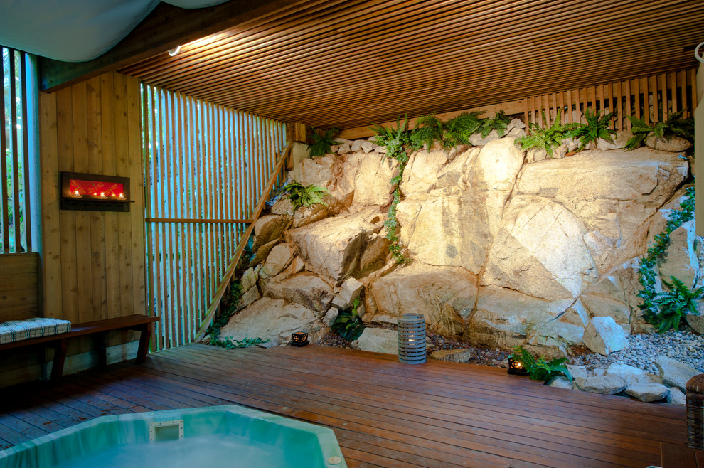 Inspiration for a mid-sized rustic round aboveground hot tub remodel in Vancouver with decking