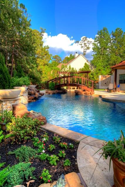 Natural Pool with rock waterfall, bridge, spa, and pergola rustic-pool