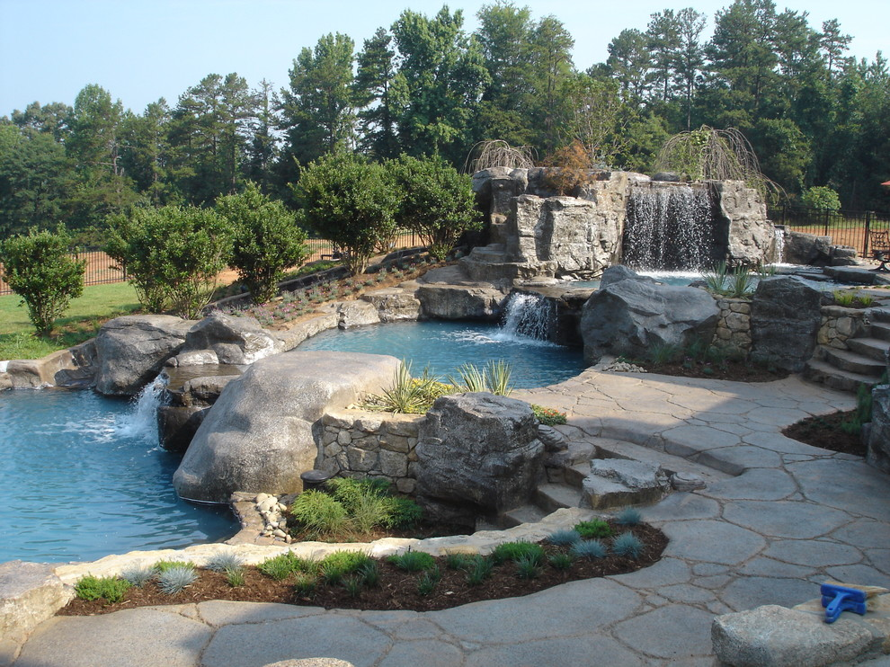 Large mountain style backyard stone and custom-shaped natural pool fountain photo in Seattle