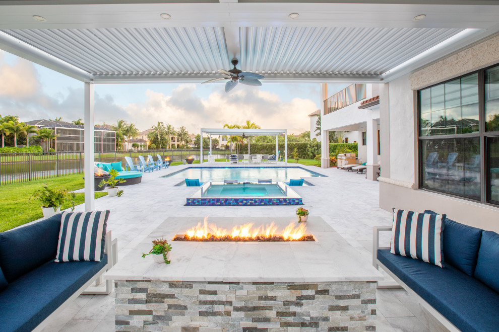 Example of a large transitional backyard rectangular and tile hot tub design in Miami