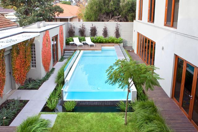 Modelo de piscina alargada, minimalista, grande, rectangular, en patio, con entablado