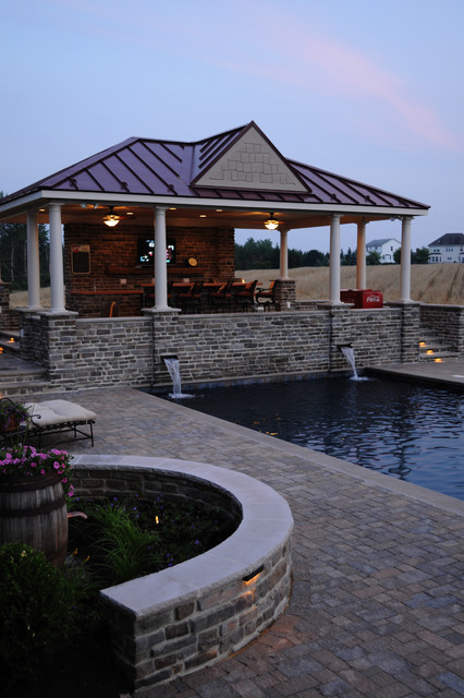 Open air pool house and pool deck at dusk traditional pool