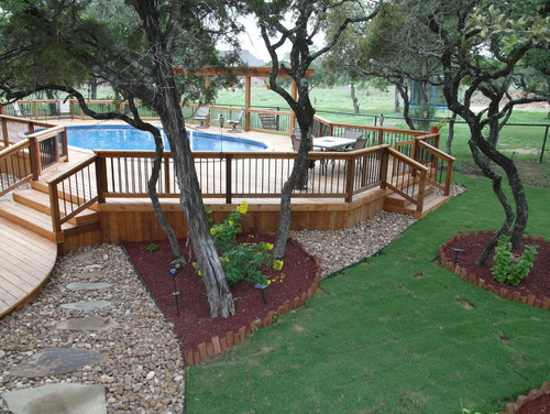 Another example of an above ground pool build into the landscaping and a deck working well with ground levels.
