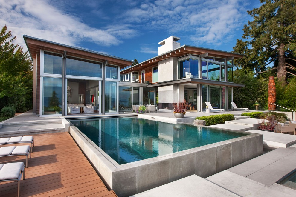 Huge trendy backyard concrete and rectangular aboveground pool photo in Seattle