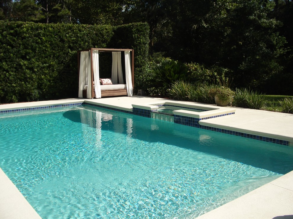Example of a mid-sized trendy concrete and rectangular pool design in Miami