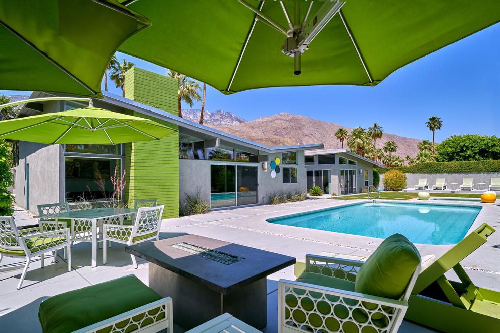 Mid-sized mid-century modern backyard rectangular pool photo in Other