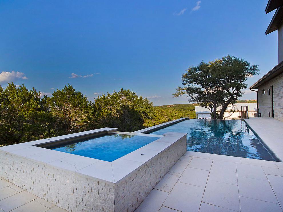 Modelo de piscinas y jacuzzis infinitos, contemporáneos, de tamaño medio, rectangulares, en patio trasero, con adoquines de piedra natural