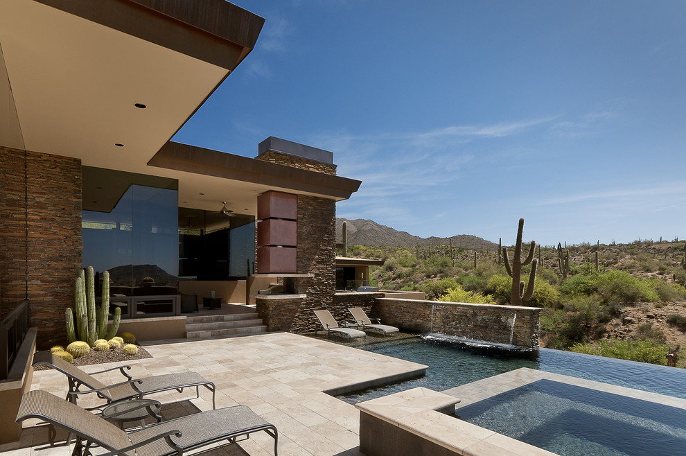 Example of a large southwest backyard custom-shaped and stone infinity hot tub design in Phoenix