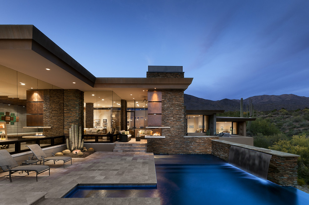 Example of a large southwest backyard custom-shaped and tile infinity pool fountain design in Phoenix