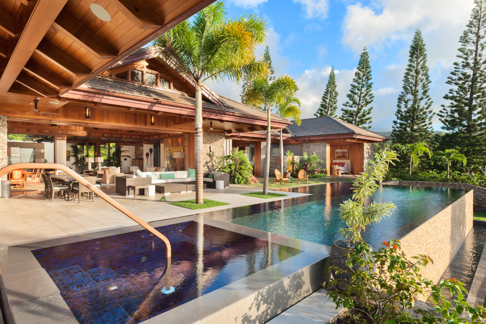 Inspiration for a large tropical backyard concrete and rectangular infinity hot tub remodel in Hawaii