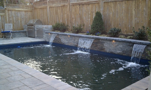 Pool and outdoor kitchen in a row house backyard. traditional-pool