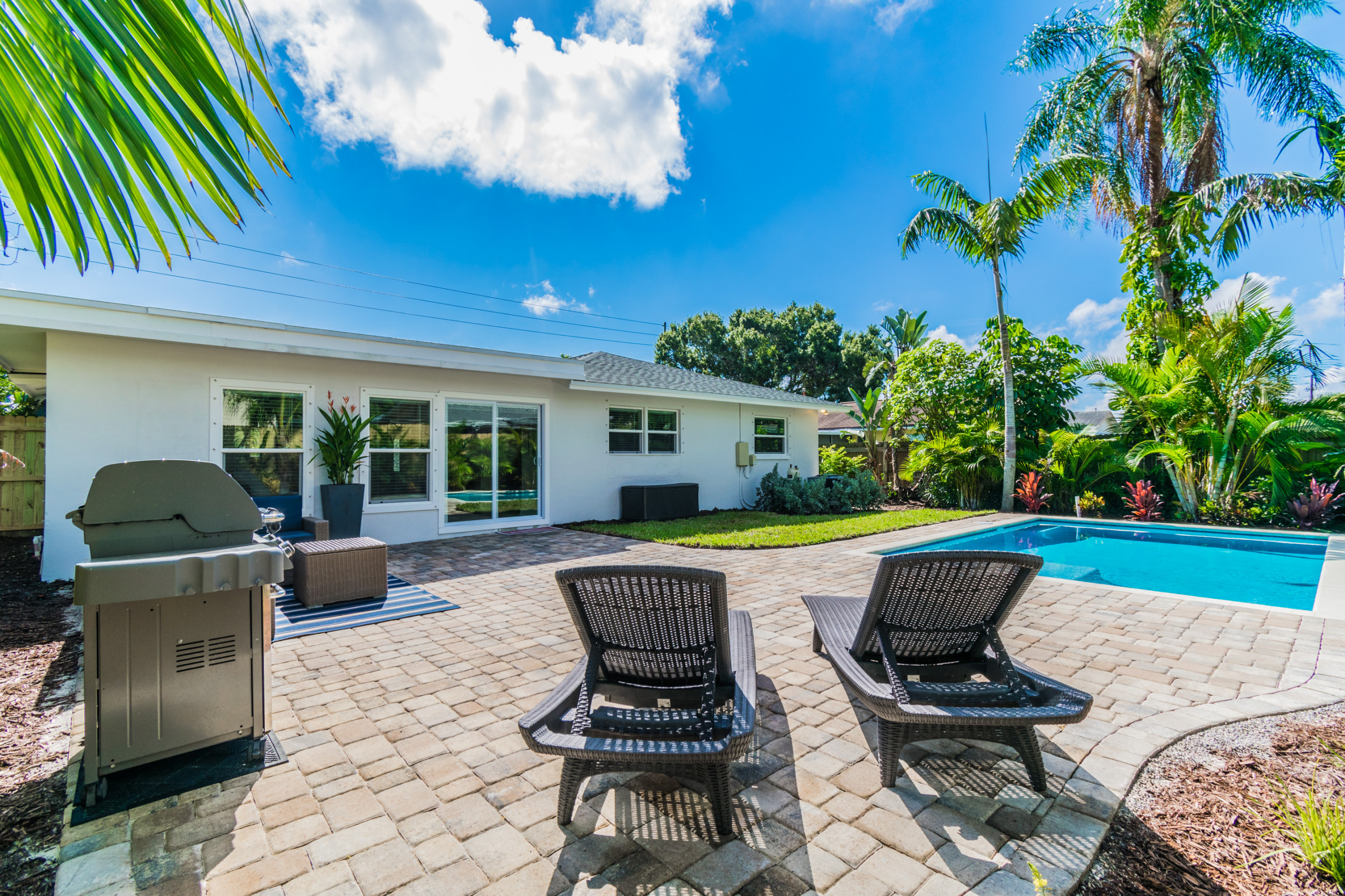 Pool and outdoor living area remodel with tropical landscaping
