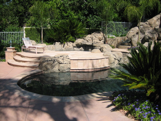 Pool and patio with stone rock walls and deck rustic for Landscaping rocks orange county