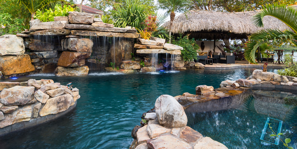 Example of a huge island style backyard stone and custom-shaped natural hot tub design in Tampa