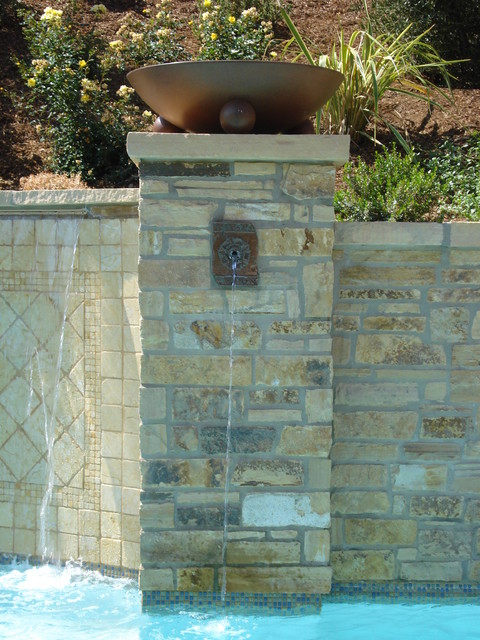 Pool wall with copper spill way and fire bowl. mediterranean-pool