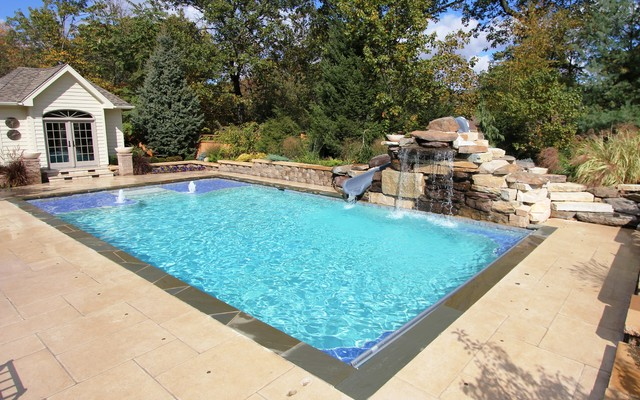 Pool with  oversized tanning ledges and fire feature water slide traditional-pool