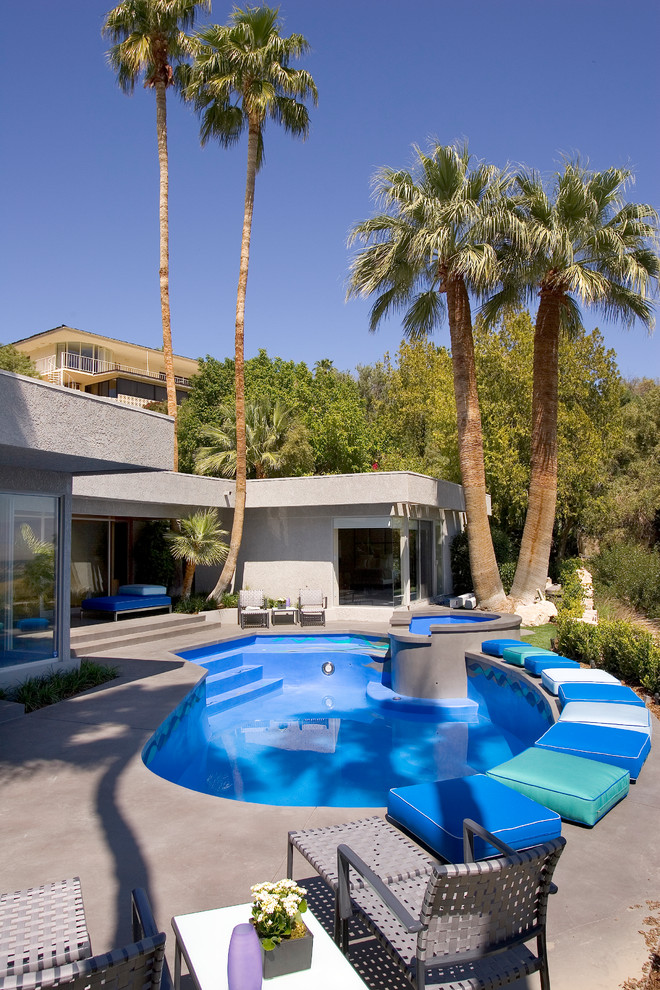 Inspiration for a tropical backyard concrete and custom-shaped pool remodel in Los Angeles