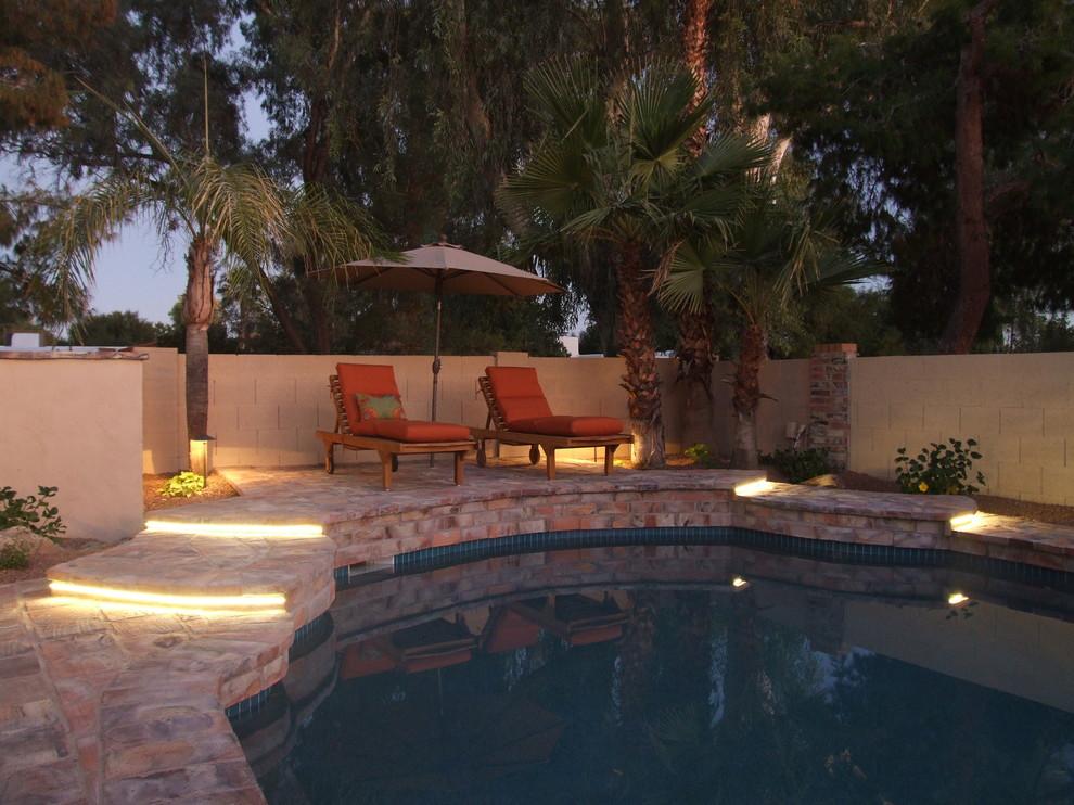 Tuscan brick and custom-shaped pool photo in Phoenix