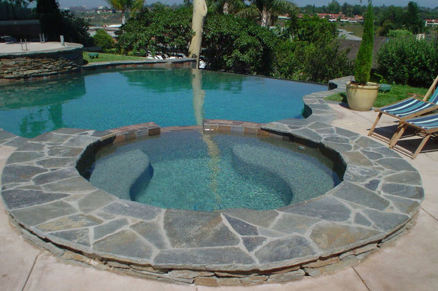 Red mountain stone coping and infinity edge pool swan for Stone swimming pool