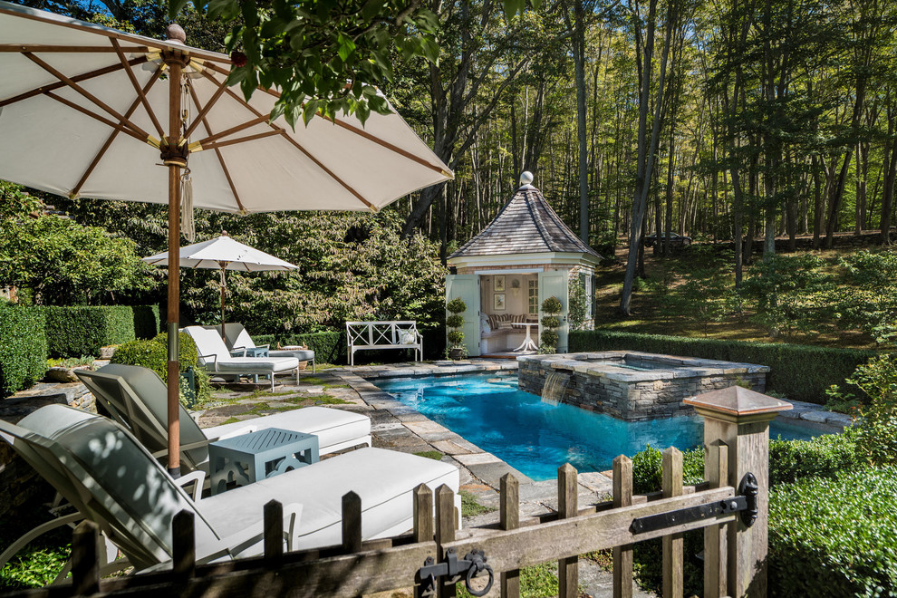 Elegant backyard stone and rectangular lap hot tub photo in New York