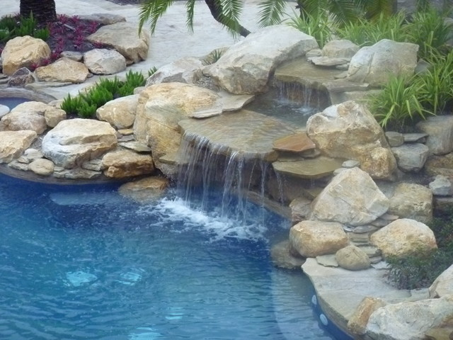 Rock waterfall and pond into swimming pool contemporary for Garden pool fountains