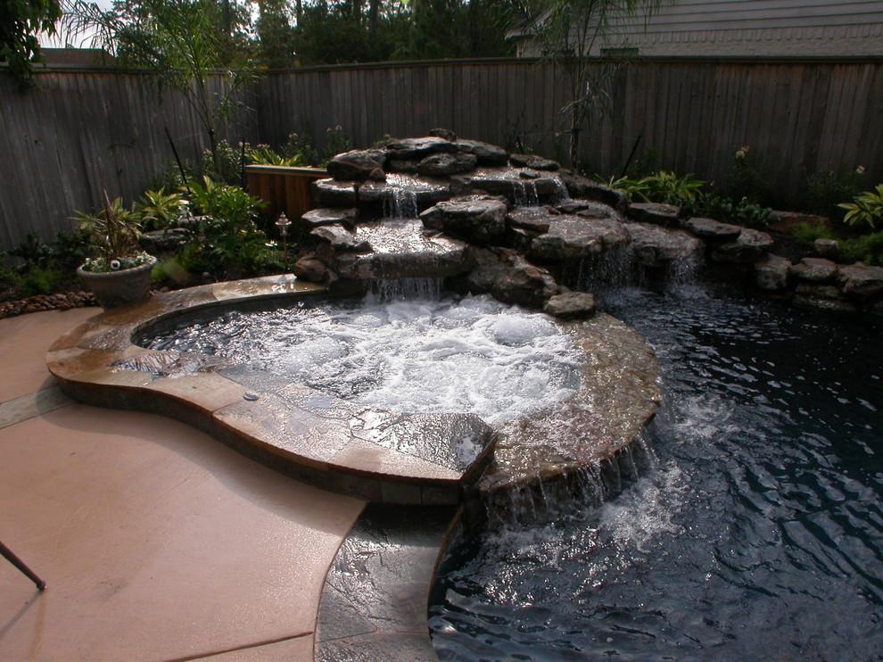 Large trendy backyard stone and custom-shaped natural hot tub photo in Houston