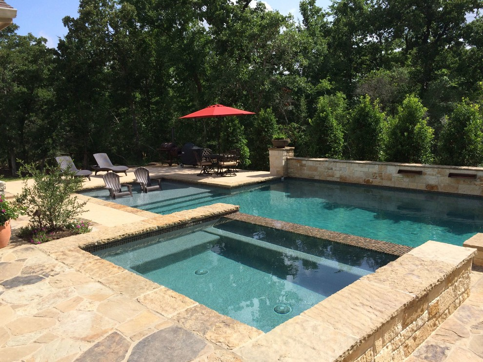 Inspiration for a mid-sized timeless backyard stone and rectangular lap hot tub remodel in Dallas
