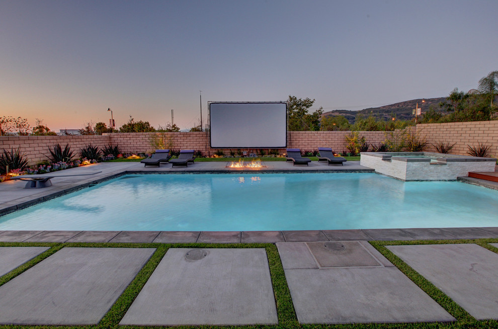 Example of a large trendy backyard rectangular and concrete lap hot tub design in Orange County