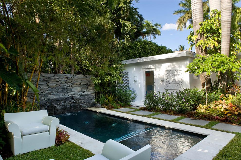 Pool fountain - small tropical backyard concrete paver and rectangular lap pool fountain idea in Miami