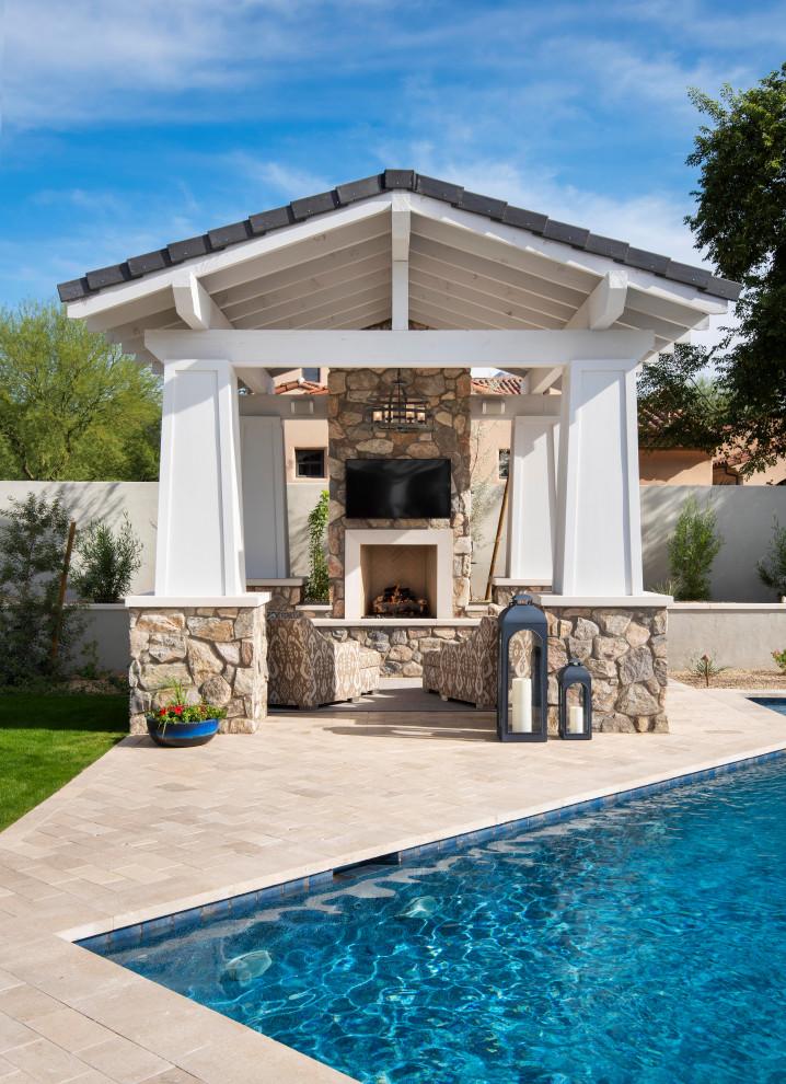 Large transitional backyard stone and custom-shaped pool house photo in Phoenix