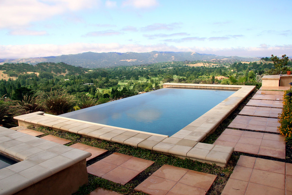 Inspiration for a large mediterranean backyard tile and rectangular infinity hot tub remodel in San Francisco