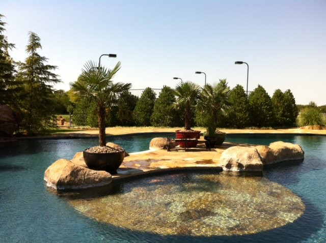Swimming pool with island and sun shelf mediterranean - Swimming pool contractors oklahoma city ...