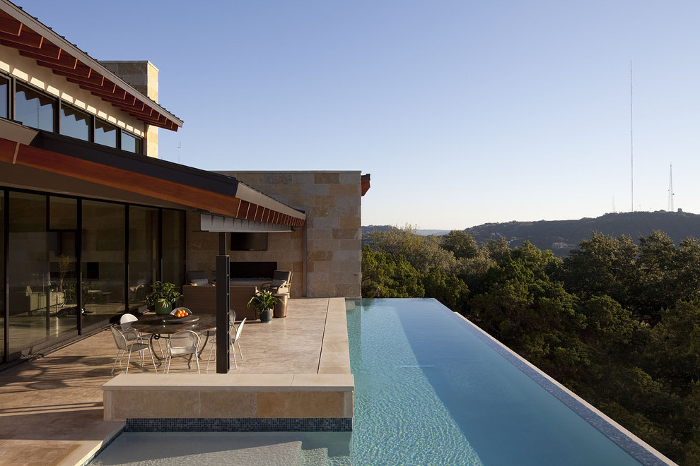 Inspiration for a large contemporary backyard tile and l-shaped infinity hot tub remodel in Austin
