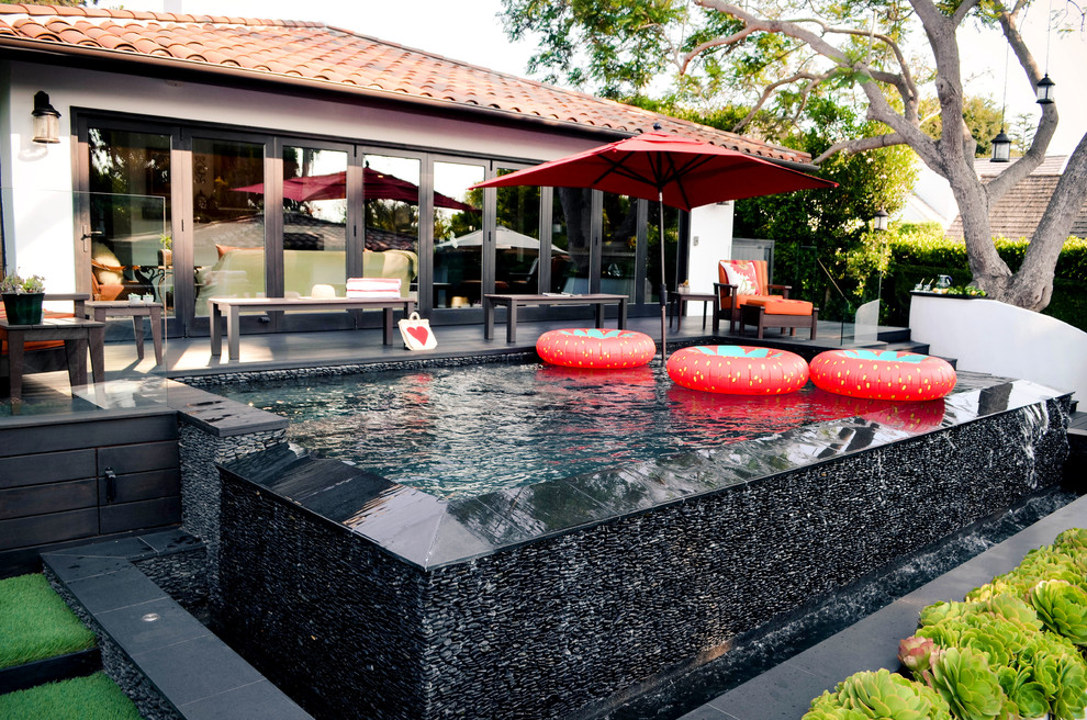Pool fountain - mid-sized mediterranean backyard rectangular infinity pool fountain idea in Los Angeles with decking
