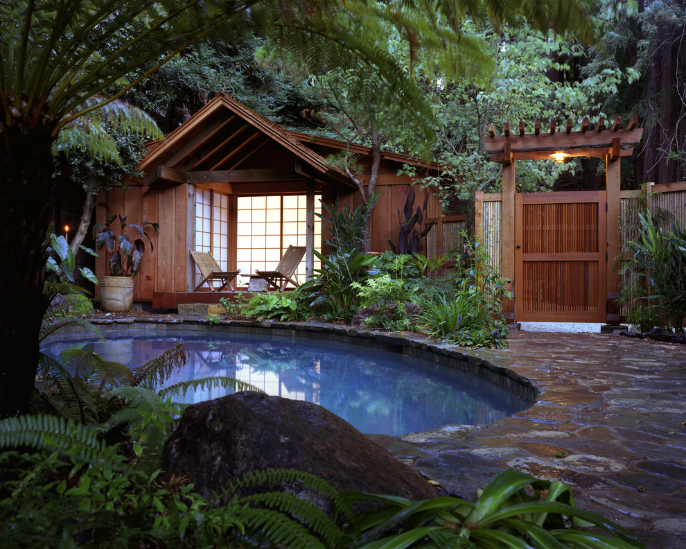 Island style stone and round pool house photo in Other