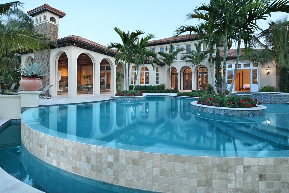 Large tuscan backyard tile and custom-shaped lap pool photo in Miami