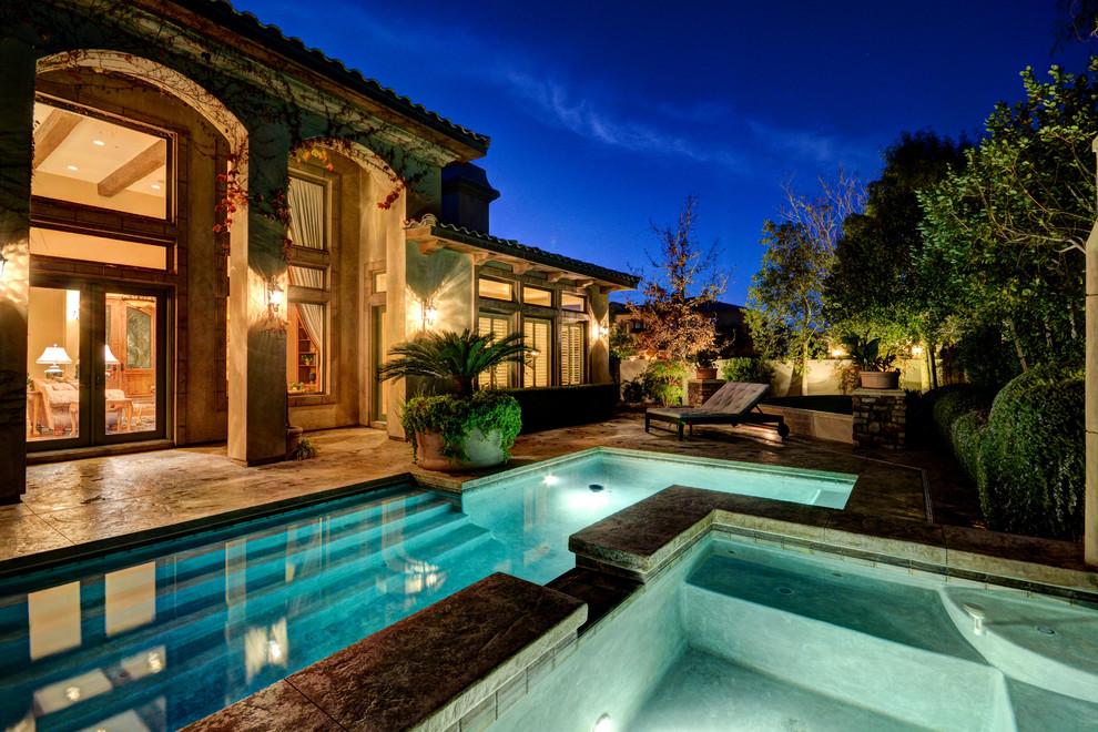 Ejemplo de piscina con fuente mediterránea, en forma de L, en patio trasero